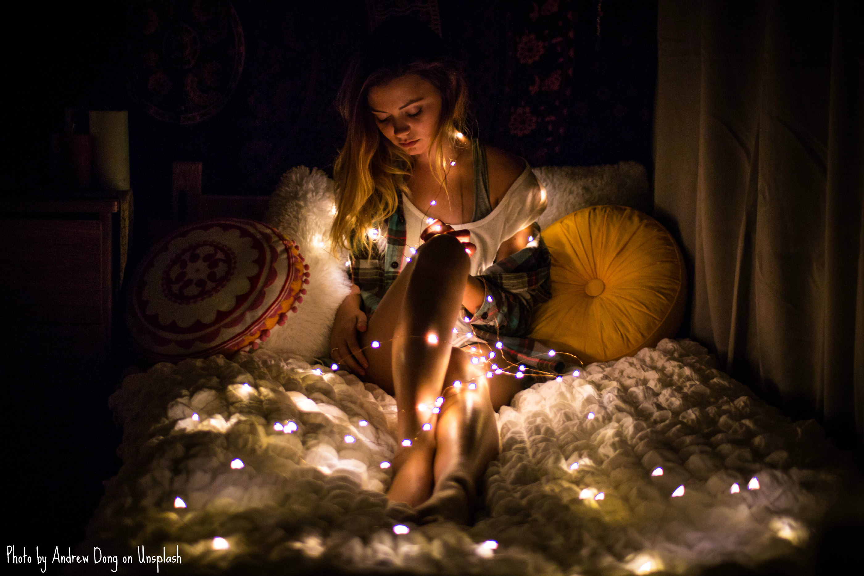 A female with blonde wavy hair and golden skin lounges on a mattress adorned with a fuzzy comforter and throw pillows. the room is dark, and she has string lights ranging from yellow to pale pink wrapped around her neck, torso, and legs. The lights are on, illuminating her in the darkness.