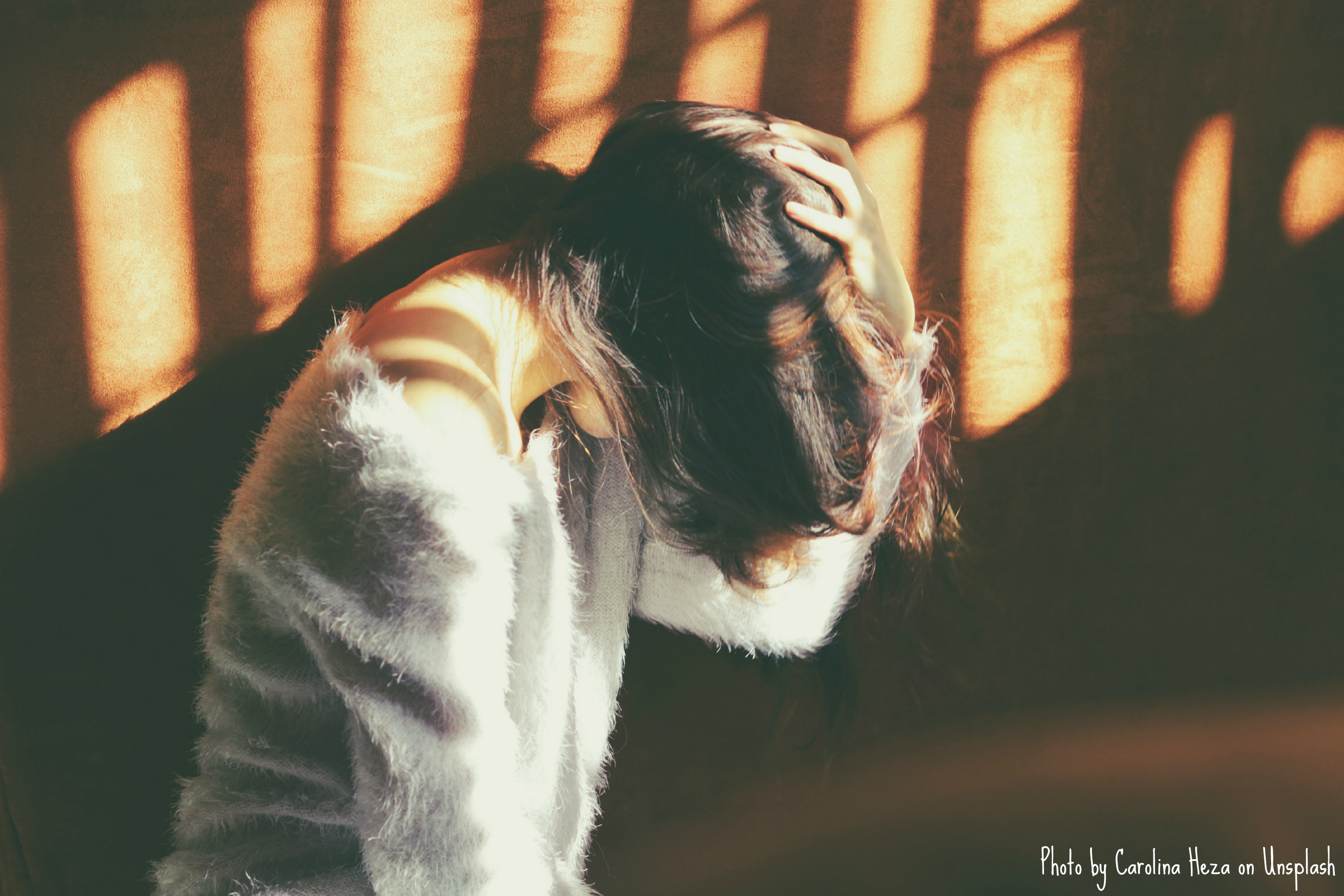 A thin person with long dark hair wearing a pale gray fuzzy top has their head buried in their left hand. The photo is a side profile of them from their right, and sunlight beams through an unseen barrier, casting shadows on them and the terra-cotta looking wall behind them.
