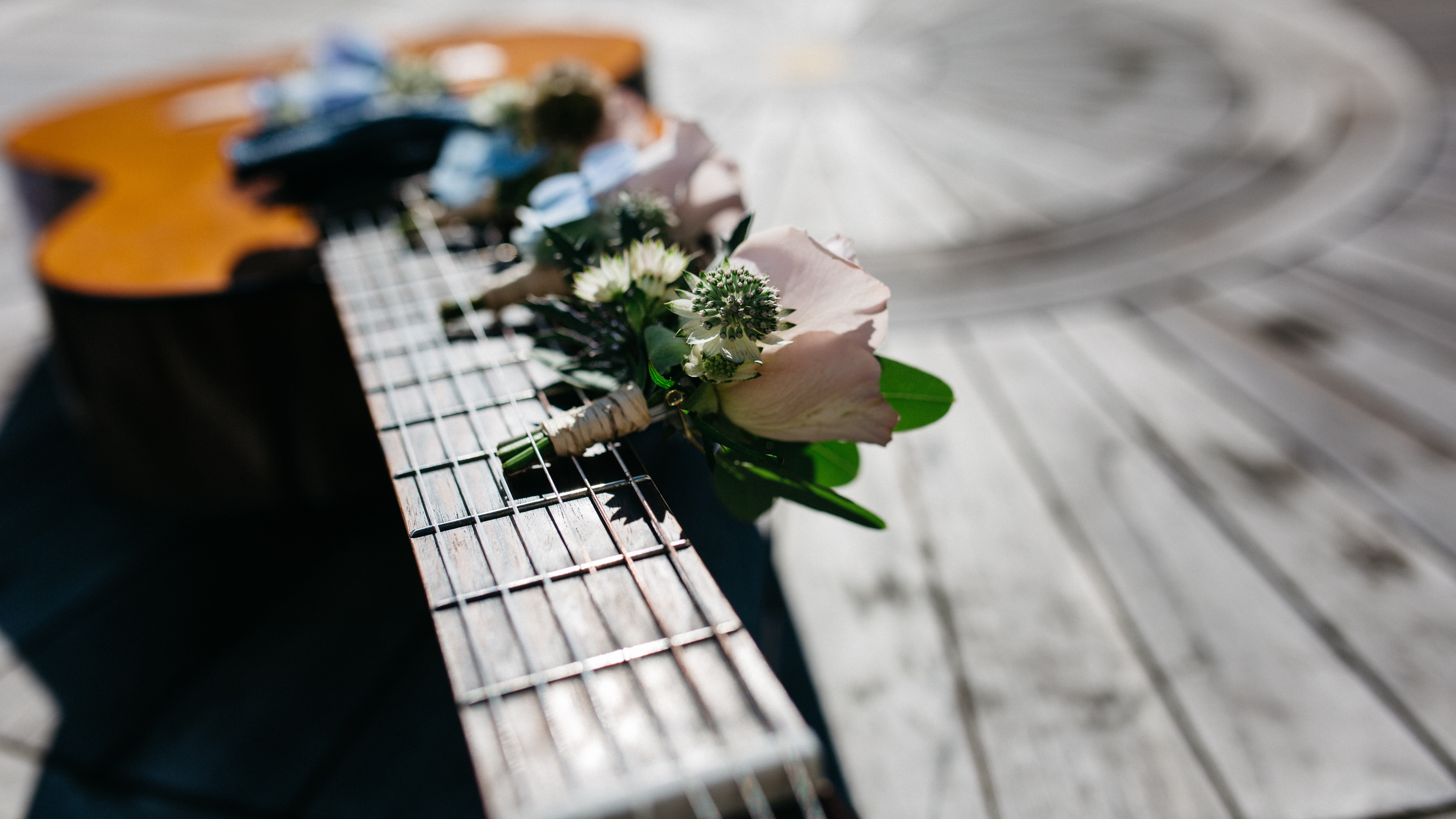 A six-stringed accoustic guitar with miniature bouquets of pale pink roses and little white flowers tucked between the strings and the neck of the instrument. Blue ribbon can be seen further along, presumably wrapped around one or more bouquets by or inside the guitar's cavity.