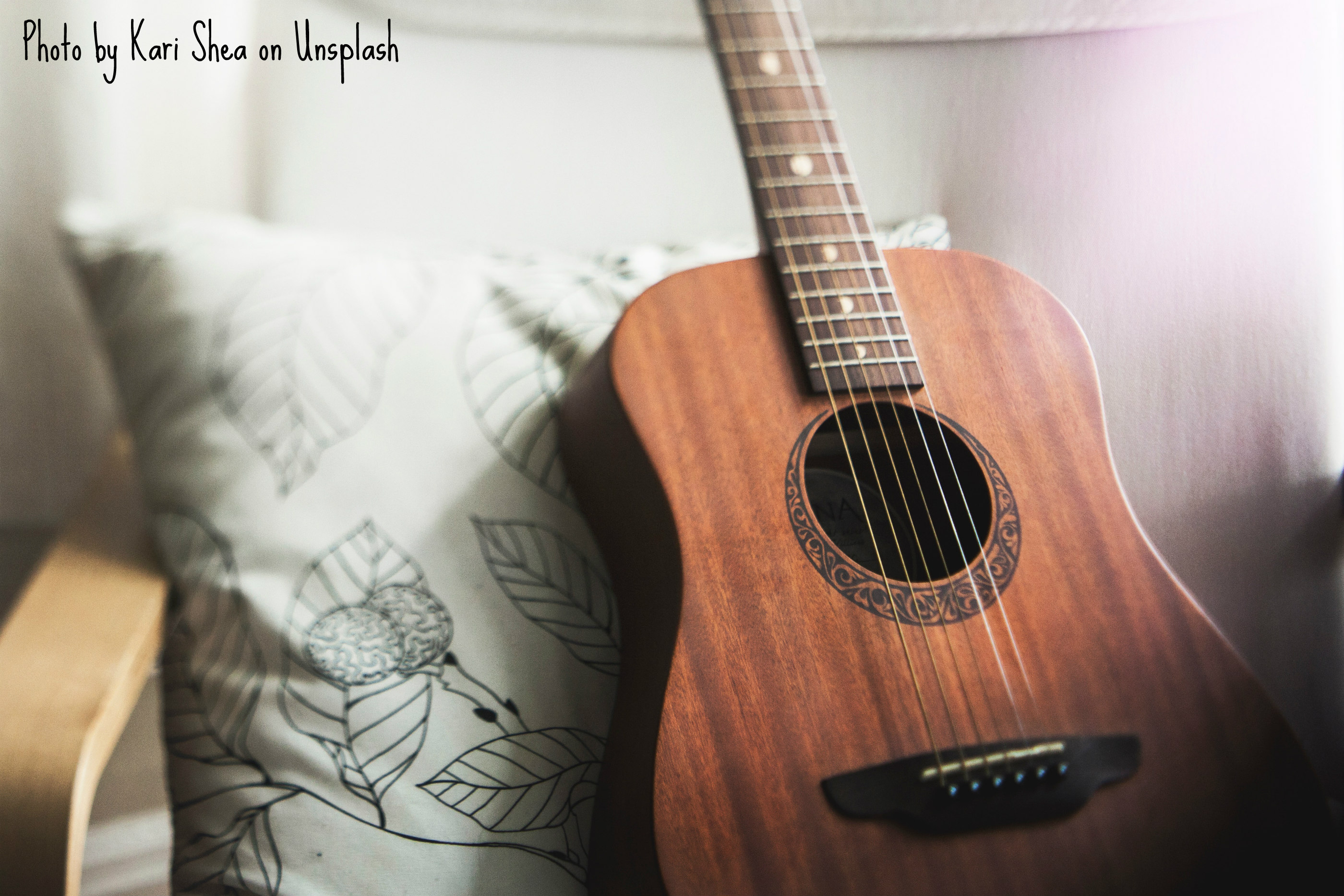 A six-stringed accoustic guitar is propped up against a white throw pillow that has leaves embroidered all over in black. A black crescent cups the sound hole, its fill pattern appearing to have a Celtic design. The crescent complements the mahogany body.