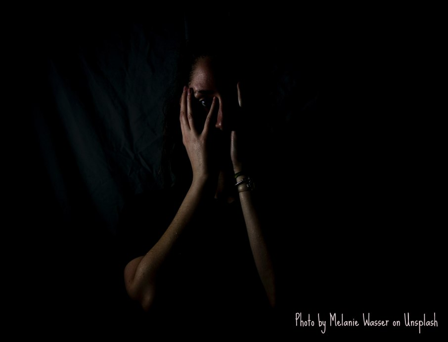 A person stands in a dark room, wearing dark clothing and covering their face with their hands; only their right eye and nose are visible. A wrinkled dark sheet hangs behind them as they gaze into the camera.