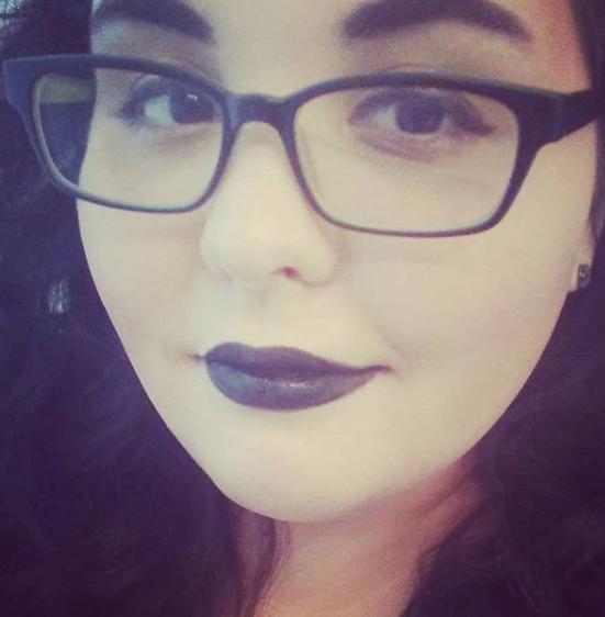 A close-up selfie of Natasha Penn. Rectangular thick-framed hipster glasses, dark wavy hair and black lips.