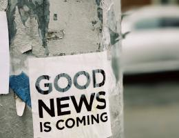"Wooden pole on the side of a road that has been painted white and has signs taped on it. The paint is peeling, revealing bluish-gray beneath, and one of the visible signs is ripped along the bottom. The main sign in focus is white with black font reading, ""Good news is coming"" in all capital letters. Out of focus in the background is a vehicle parked before a building. The building is red, presumably brick, and the car looks to be either white or silver. All the signs on the pole are wrinkled, with the main one showing signs of water damage."