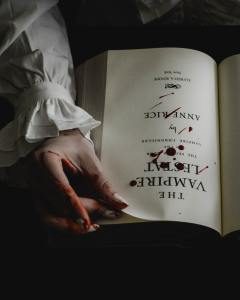 """Anne Rice's """"The Vampire Lestat"""" novel lies open on the main title page. A hand holds the top corner between two blood-stained fingers, eager to turn the page. Drops of blood are splattered across the center of the page."""