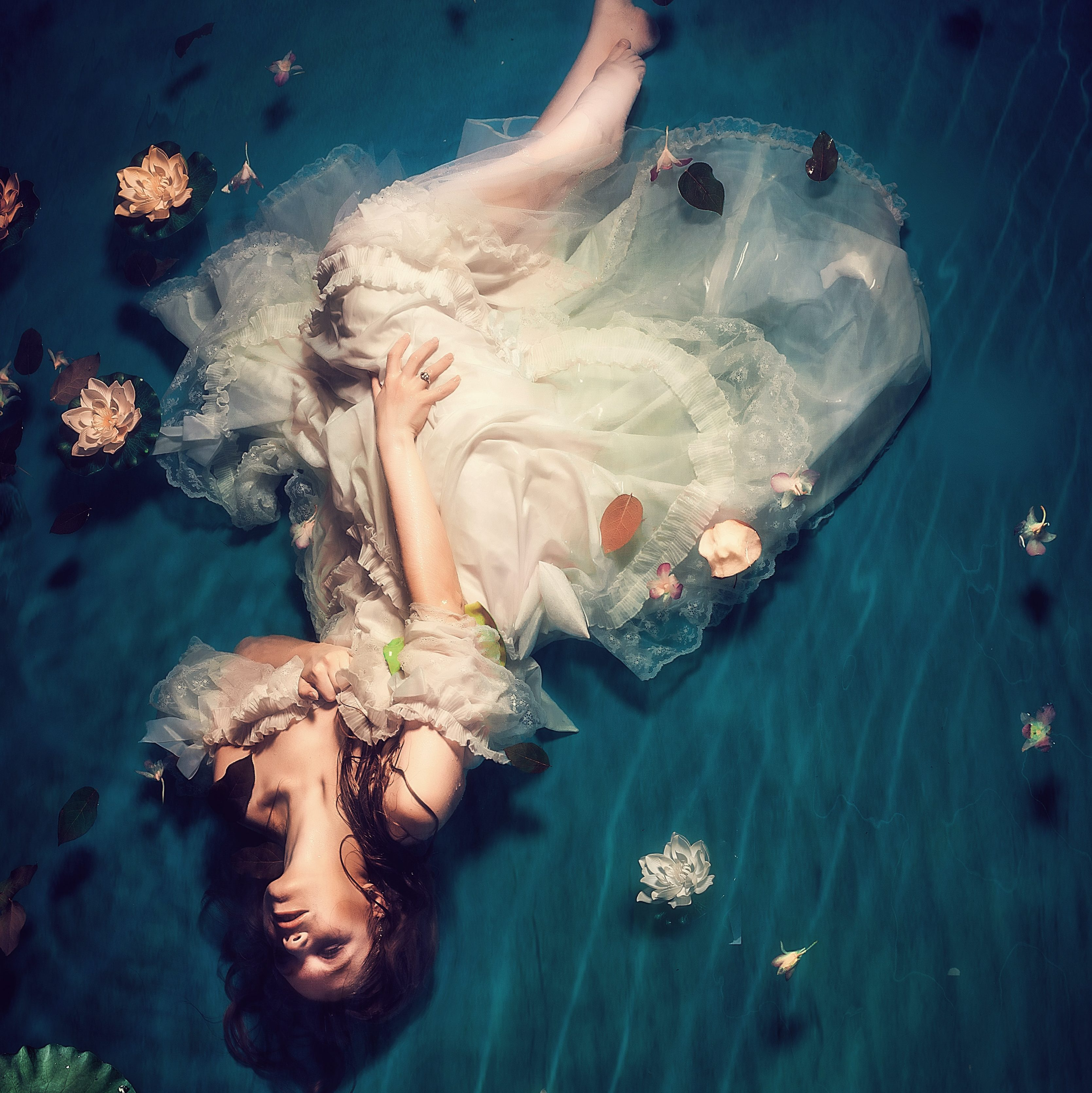 A feminine figure in a white dress is floating in a pool of water. Lotuses, lilies, and lily pads float around them.