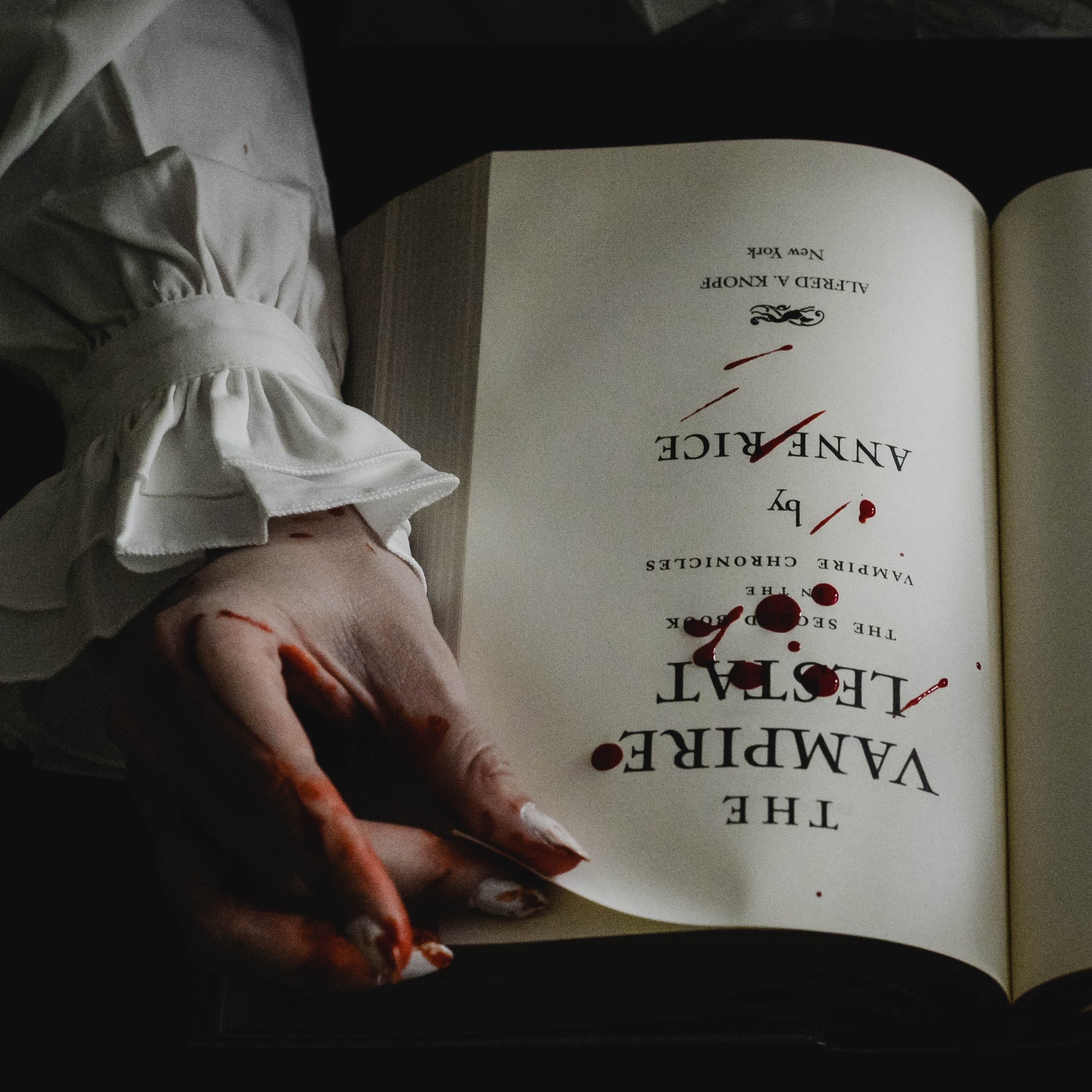 "Anne Rice's ""The Vampire Lestat"" novel lies open on the main title page. A hand holds the top corner between two blood-stained fingers, eager to turn the page. Drops of blood are splattered across the center of the page."